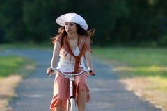 Retro meisje op oude fiets stock foto's