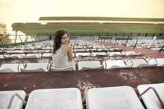Retro meisjeszitting in stadion Stock Fotografie