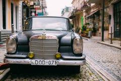 Retro- Mercedes Benz Car Parked On Narrow gepflasterte Straße Front View Of Black Raritys Lizenzfreie Stockbilder