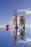 Retro- Messingmusikinstrumente auf Spiegel und Apfel Stockfoto