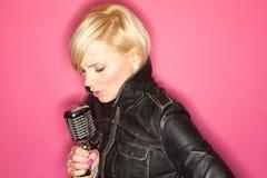 Retro mic. Blonde pop star on pink background singing , holding retro mic Stock Photography