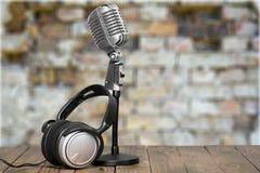 Retro microfono e cuffie di stile su di legno immagini stock