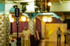 Retro microfoon bevindt zich in een restaurant op de achtergrond van het binnenland van de zaal De microfoon is voorgenomen voor stock foto's