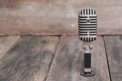 Retro Microfoon Uitstekende stijl op de houten vloerachtergrond stock afbeeldingen