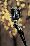 Retro microphone. Retro chrome microphone with warm bokeh background