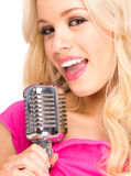 Retro microphone. Pop female blonde wearing pink singer with the retro microphone Royalty Free Stock Photography