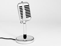 Retro Microphone. An old style fat boy microphone for singing, comedy, stage, recording lit from the side on a plain background royalty free stock photos