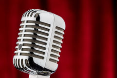 Retro microphone against red velvet Royalty Free Stock Photos