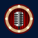 Retro microphone on a background of red curtains stock photography