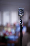 Retro microphone on a blur background. Retro microphone against blur colorful light restaurant background Stock Images