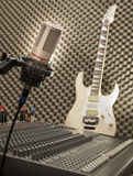 Retro microphone. With an e-guitar in the background Royalty Free Stock Images