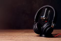Retro microphone and headphones on table against dark background royalty free stock photography