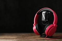 Retro microphone and headphones on table against dark background stock images