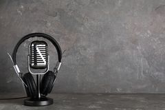 Retro microphone and headphones on table against grey background. Space for text stock photo