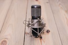 Retro microphone mounted on a wooden platform with a volume of stock photos