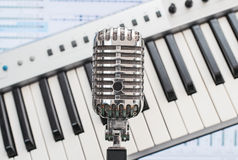 Retro microphone over piano. Stock Photography