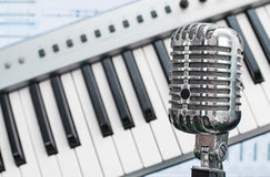 Retro microphone. Retro microphone over piano and recording software background royalty free stock photo