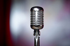 Retro microphone and red curtain. A microphone on stage over a red background royalty free stock photography