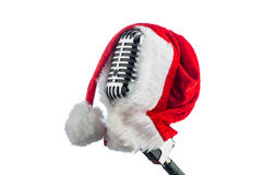 Retro microphone with santa hat. An old retro microphone with santa hat against a red velvet background Royalty Free Stock Photo