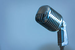 Retro microphone. Single retro microphone on blue background stock photography