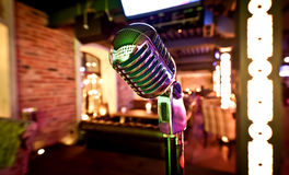 Retro microphone on stage. In restaurant. Blurred background Royalty Free Stock Photos