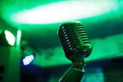 Retro microphone on stage. Retro microphone against blur colorful light restaurant background Royalty Free Stock Photography