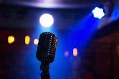 Retro microphone on stage. Retro microphone against blur colorful light restaurant background Stock Photo