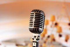 Retro microphone on stage. Retro microphone against light restaurant background on stage royalty free stock photo