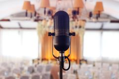 Retro microphone on stage. Retro microphone against light restaurant background on stage stock photo