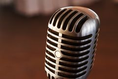 Retro microphone on stage. Retro microphone against light restaurant background on stage stock image