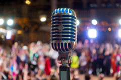 Retro microphone on the stage. Blurred audience at background Stock Photos