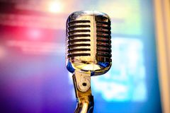 Retro microphone on stage. Close up and lighting in background Royalty Free Stock Photography