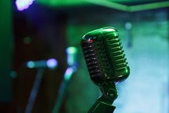 Retro microphone on stage. Retro microphone against blur colorful light restaurant background Stock Photography