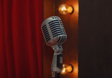 Retro microphone on stand on the background of red curtain Royalty Free Stock Images