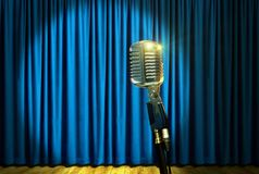 Retro microphone on stage over blue curtains Stock Photography