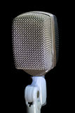 Retro Microphone Vertical. Retro Microphone on stand with black background royalty free stock photos