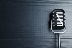 Retro microphone on wooden background, top view. With space for text royalty free stock photos