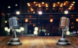 Retro microphones on wooden table. Blured background and blue sky with lights Stock Images