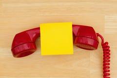Retro microtelefono rosso del telefono con la nota appiccicosa sullo scrittorio di legno strutturato immagine stock libera da diritti