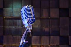 Retro- Mikrofon auf hölzernem braunem Hintergrund Stockbild