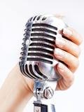 Retro- Mikrofon in der Hand der Frau Stockfotografie