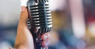 Retro mikrofon i hand på suddig bakgrund Royaltyfria Foton