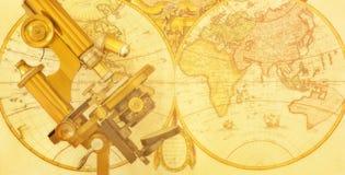 Retro mikroskop med världskartan royaltyfri foto