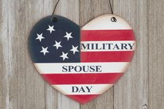 Retro Military Spouse Day heart sign on weathered wood. Retro Military Spouse Day heart sign with the colors of the USA flag on weathered wood royalty free stock photography