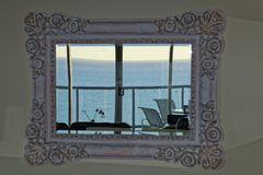 Free Retro Mirror In Living Room With View To Ocean From Top Floor Apartment Stock Photo - 158907960