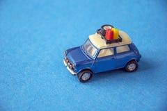Retro modell för leksakbil på blå bakgrund Tappningbil i miniatyr Royaltyfria Foton
