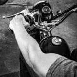 Retro motorbike. Black white picture of a muscular biker royalty free stock photo