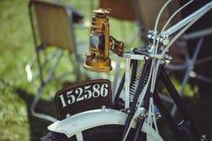 Retro motorfiets, de koplamp van de messingskerosine van een oude motorfiets, aanzetsteen voorvork en een oud aantal, vooreind stock fotografie