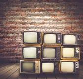 Retro mucchio delle televisioni sul pavimento nella vecchia stanza fotografia stock libera da diritti