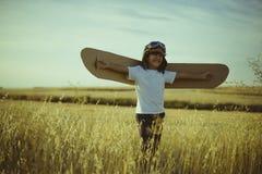Retro, muchacho que juega para ser piloto del aeroplano, individuo divertido con el aviador fotos de archivo